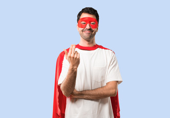 Superhero man with mask and red cape presenting and inviting to come with hand. Happy that you came on isolated blue background