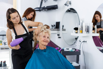 Hairdresser drying hair of elderly female