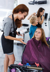 Hairdresser drying hair of teen girl