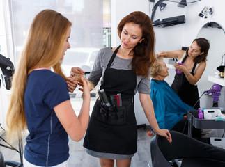 Hairdresser inspecting hair of girl