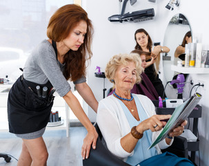 Elderly female with magazine discussing with hairdresser