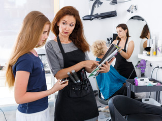 Hairdresser with teen girl looking at magazine
