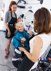 Hairdressers finished haircut for senior woman