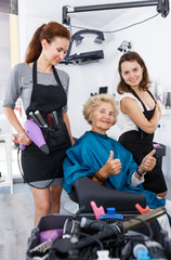 Hairstylists presenting result of styling to female client