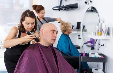 Hairdresser doing styling of man