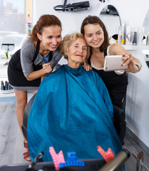 Hairstylists and female customer taking selfie