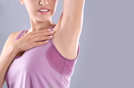 Young woman with sweat stain on her clothes against grey background, space for text. Using deodorant