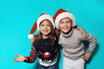Cute children in warm sweaters and Christmas hats on color background
