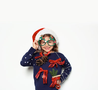 Cute little girl in handmade Christmas sweater and hat with party glasses on white background