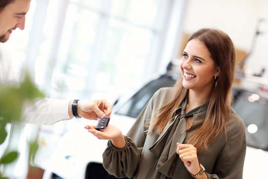 Happy young woman buying car in showroom