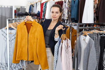 Woman holding lot of hanger with clothes