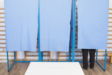 Person voting in booths at a polling station
