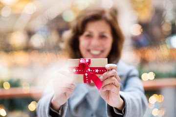 A senior woman with a present in shopping center at Christmas time.