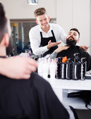Happy man forming beard of client into shape