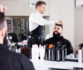 smiling male stylist creating haircut for man client at hairdressing salon