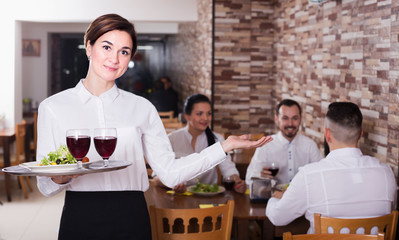 Smiling woman waitress carrying order for guest