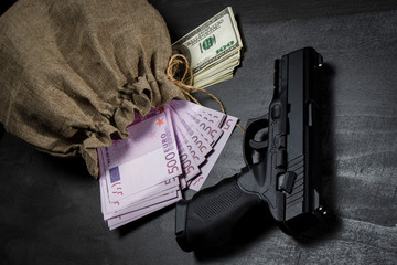 Pistol on the table near the bag with dollars and euros