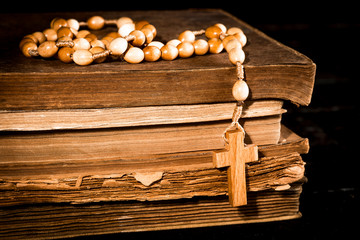 Rosary on a background of books on old boards