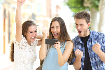 Excited friends watching media from smartphone
