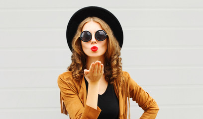 Portrait pretty woman sends air sweet kiss in black round hat, sunglasses and brown jacket on gray wall background