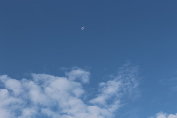 The moon is visible in the afternoon on the blue sky