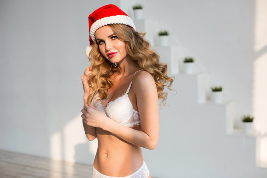 Beautiful sexy woman in lingerie and Santa hat at home.