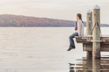 Woman sitting on the pier at the lake
