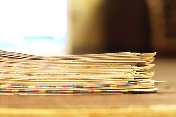 Texture of old newspapers with folded yellow pages in big stack with blurred background, close up