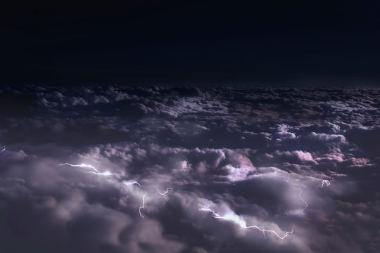 view from the window of the plane to the clouds at night and flashes of lightning