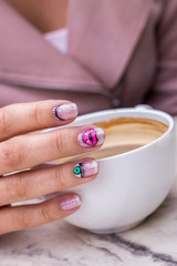 nail art manicure with colorful polish nails and cup of coffee. Beauty hands and stylish nails.