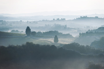 Spectacular view with italian autumn foggy fields in tuscany valleys