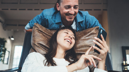 Couple sitting together in leather couch and taking selfie photos using mobile phone camera. Multiethnic young family