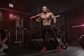 Young handsome athlete bodybuilder, weightlifter, doing crossfit, with a sledgehammer, in a modern gym. Concept-strength, beauty, power, sport, health, sports nutrition, diet, styroydy, scales.