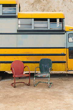 Two metal chairs outdoors against school bus