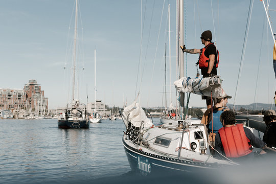 ships leaving marina in the city to begin a yacht race at sea