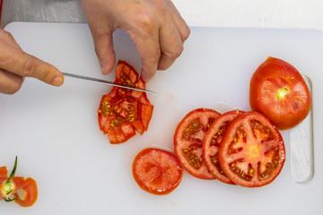 Person cutting a tomato