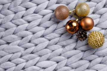 Christmas wooden decor on gray background with cones, toys, balls and woolen plaid