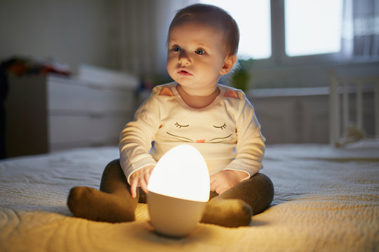 Adorable baby girl playing with bedside lamp in nursery