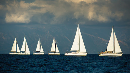 Sailing boats participate in yachting regatta among Greek islands in the Aegean Sea in stormy weather.