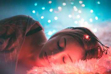 Close-Up Of Young Woman Sleeping In Illuminated Room