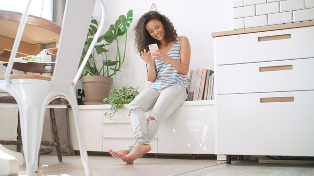 Charming young brunette woman using phone at modern home.