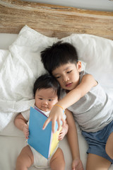 Brother and his baby sister reading on bed