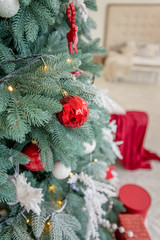 Gifts under decorated christmas tree with red balls. Close up