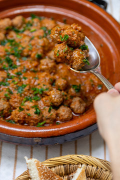 Person scooping up meatballs to eat