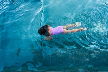 Girl Swimming In The Water With A Pink Bathing Suit