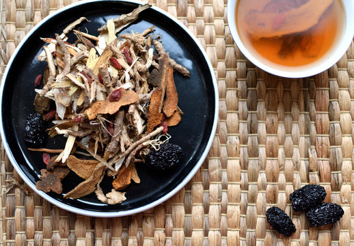 Chinese traditional medicine script. Herbal tea with jujubes, goji berries, gingseng roots and others on neutral background.