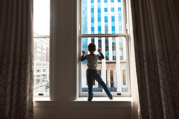 A Sihouette Of A Boy Standing In Front Of A Window In The Middle Of A City