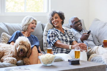 Multiethnic seniors drinking, socializing and watching TV together at home