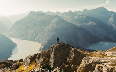 Hiker watching to Sun at horizon. Beautiful moment the miracle of nature. Colorful mist in valley. Man hike. Mountain Pass in Switzerland. Autumn mood at sunset.