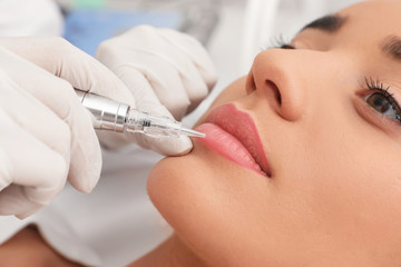 Young woman undergoing procedure of permanent lip makeup in tattoo salon, closeup